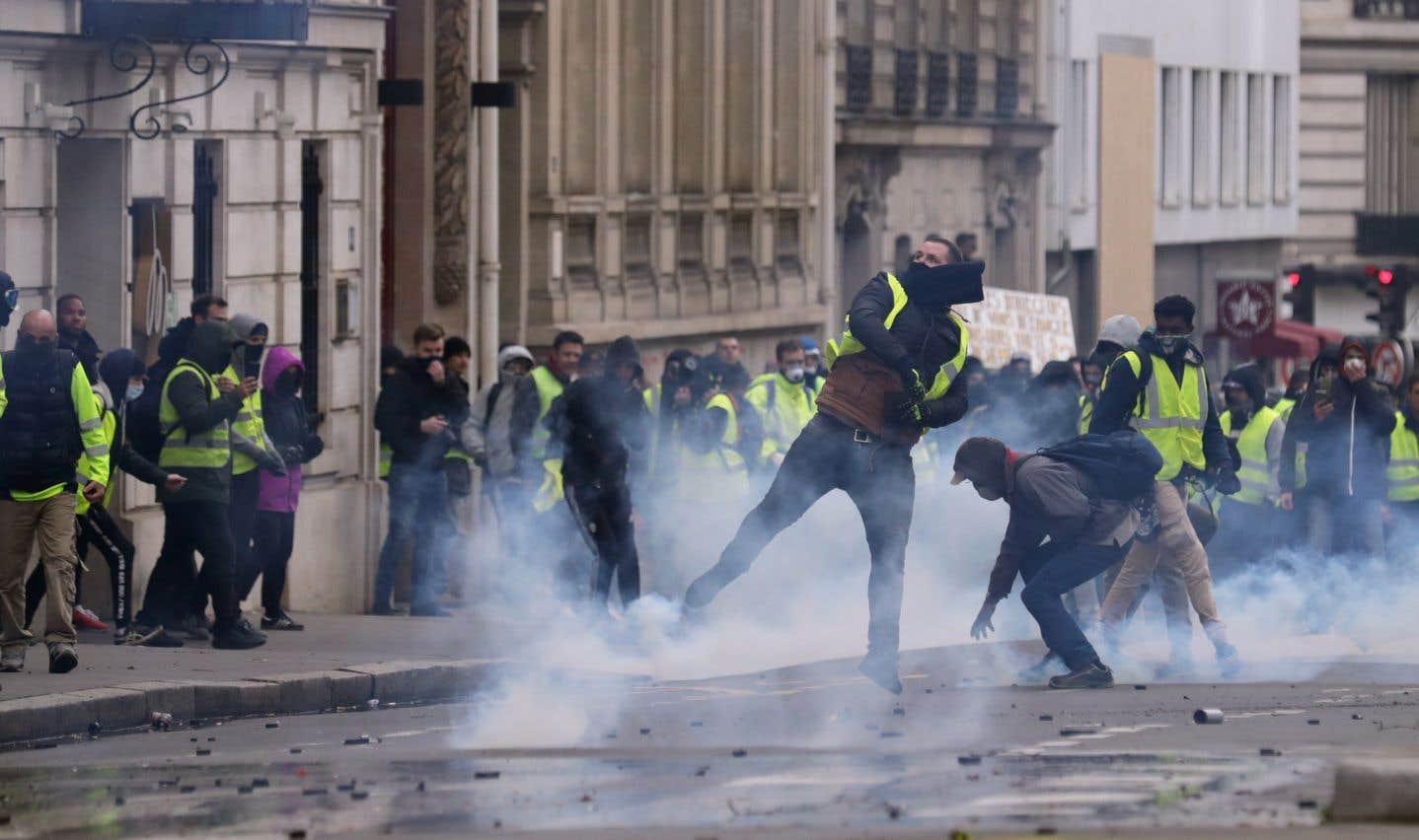 Des manifestants lancent des morceaux de pavé vers les policiers anti-émeute, au milieu de gaz lacrymogènes, près des Champs-Élysées, à Paris.