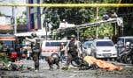 Des policiers examinaient les lieux après l'attaque survenue à l'extérieur de l'église pentecôtiste du centre de Surabaya, dimanche. Des démineurs y ont aussi désamorcé deux autres bombes.