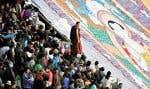 Malgré les exactions du gouvernement chinois, le bouddhisme tibétain résiste. Sur la photo, un moine boudhiste se tient entre les fidèles et un thangka (broderie religieuse) géant déployé au début de cette semaine au monastère de Drepung, près de Lhasa, dans la Région autonome du Tibet.