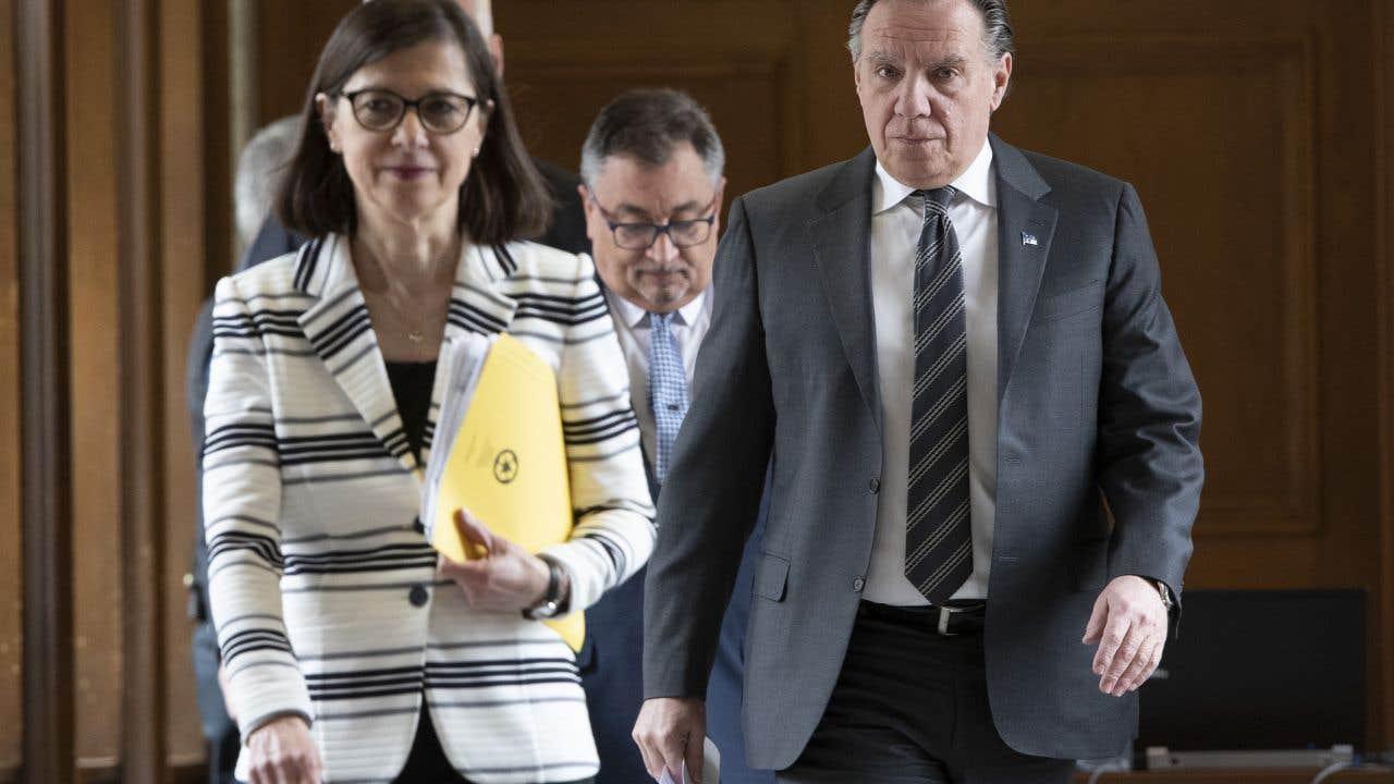 La ministre de la Santé Danielle McCann, le premier ministre François Legault et, derrière eux, le directeur nationale de la Santé publique, Horacio Arruda.
